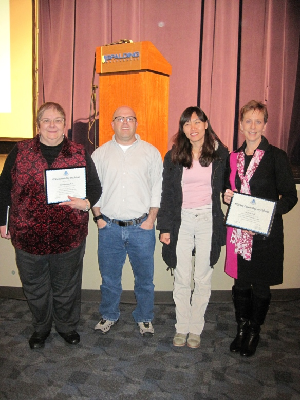 Kathy Klueber of Spalding University and Jamie Beach are presented with Darwin Day Roadshow certificates by Jory and Mira